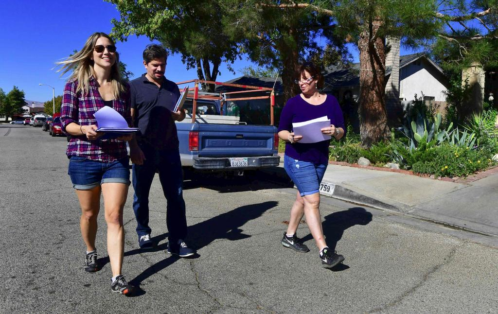 Talia Osteen, Ari Posner et Becky Edwards, des volontaires devenus actifs politiquement après l'élection de Donald Trump, en novembre 2016.  three first time volunteers who became politically active following last November's US presidential elections, walk through a quiet residential neighborhood on a Saturday morinng in Palmdale, California on October 28, 2017, going door to door trying to register voters. / AFP PHOTO / FREDERIC J. BROWN / TO GO WITH AFP STORY BY VERONIQUE DUPONT-»In California, new grassroots activists lead the Trump Resistance»