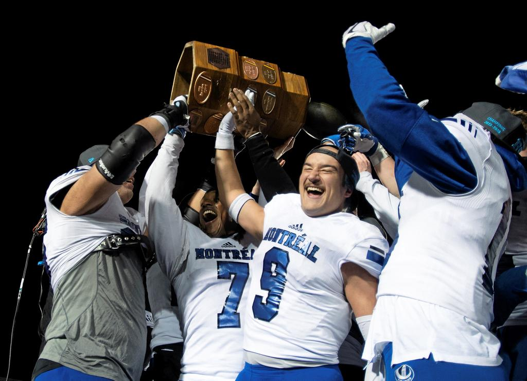 Montreal Carabins players celebrate with the trophy at the end of the Dunsmore Cup final against Laval University Rouge et Or, Saturday, November 9, 2019 at Laval University in Quebec City. From the left, Pier-Olivier Lestage, Brian Harelimana, and Jean-Sebastien Belisle. Montreal University Carabins won 25-10. THE CANADIAN PRESS/Jacques Boissinot