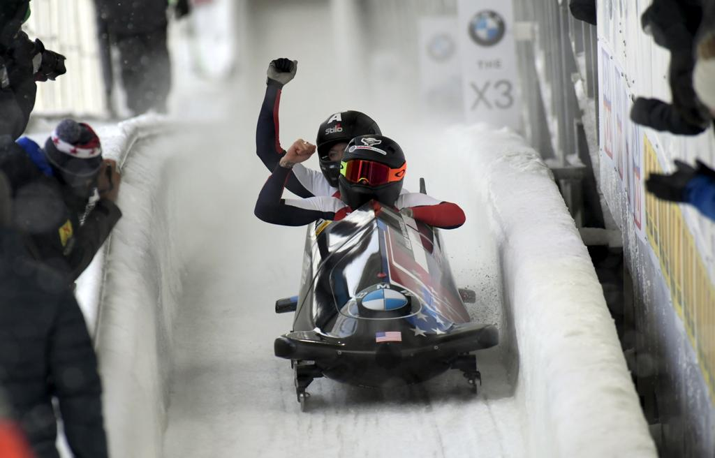 Driver Kaillie Humphries, front and brakeman, Lauren Gibbs, of The United State celebrate a first place finish after the second run of the women's World Cup bobsled opener in Lake Placid, N.Y., on Saturday, Dec. 7, 2019. (AP Photo/Hans Pennink)