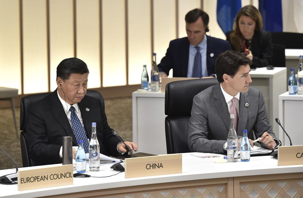 China's President Xi Jinping, left, and Canada's Prime Minister Justin Trudeau, right, attend the session 3 on women's workforce participation, future of work, and aging societies at the G-20 Summit in Osaka Saturday, June 29, 2019 (