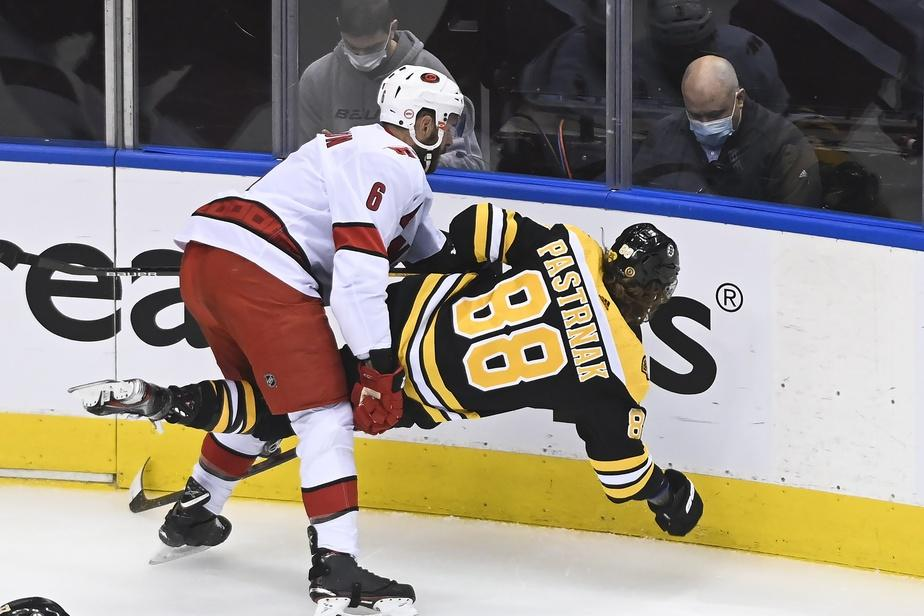 Joel Edmundson (6) met en échec David Pastrnak (88) des Bruins de Boston.