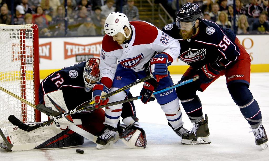 Columbus Blue Jackets' Sergei Bobrovsky, left, of Russia, makes a save against Montreal Canadiens' Andrew Shaw as Blue Jackets' David Savard defends during the third period of an NHL hockey game Thursday, March 28, 2019, in Columbus, Ohio. (AP Photo/Jay LaPrete)