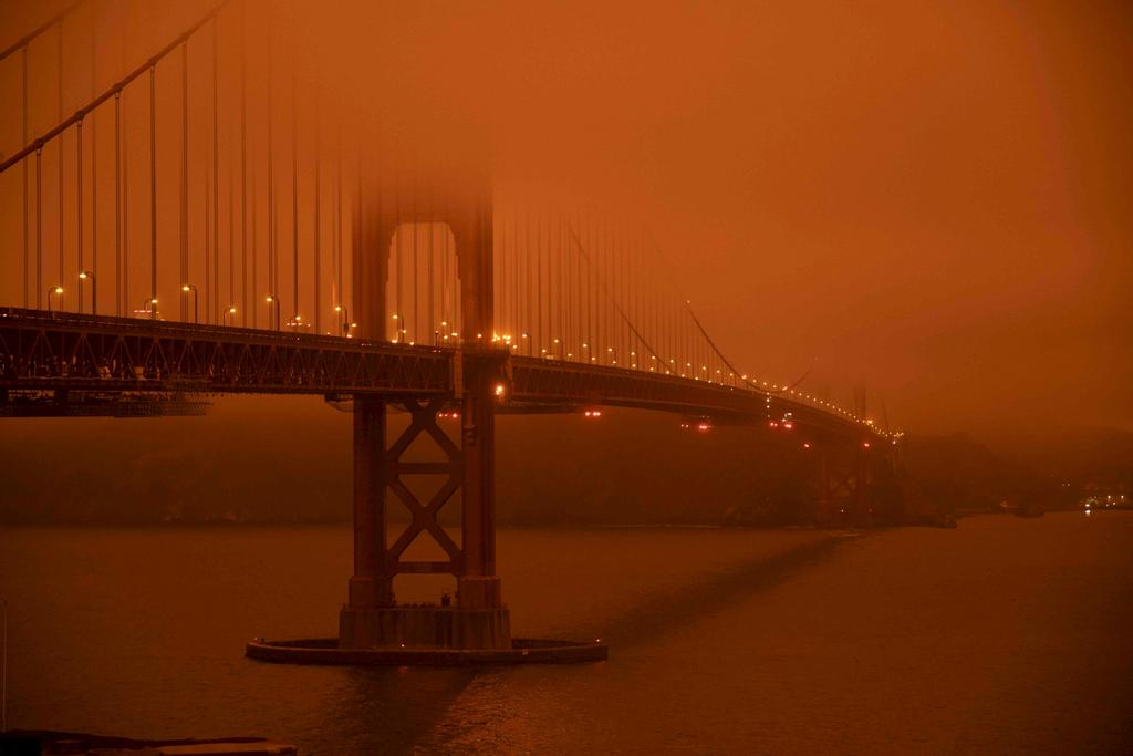 Cars drive along the Golden Gate Bridge under an orange smoke filled sky at midday in San Francisco, California on September 9, 2020
