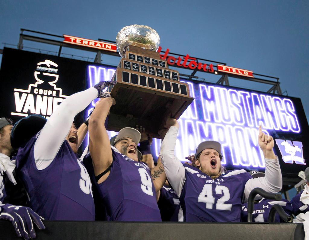 Western Mustangs' Andrew Thurston (42) and Myles Manalo (9) hold up the Vanier Cup as they celebrate with teammates after defeating the Laval Rouge et Or in Hamilton, Ont., on Saturday, November 25, 2017. THE CANADIAN PRESS/Peter Power