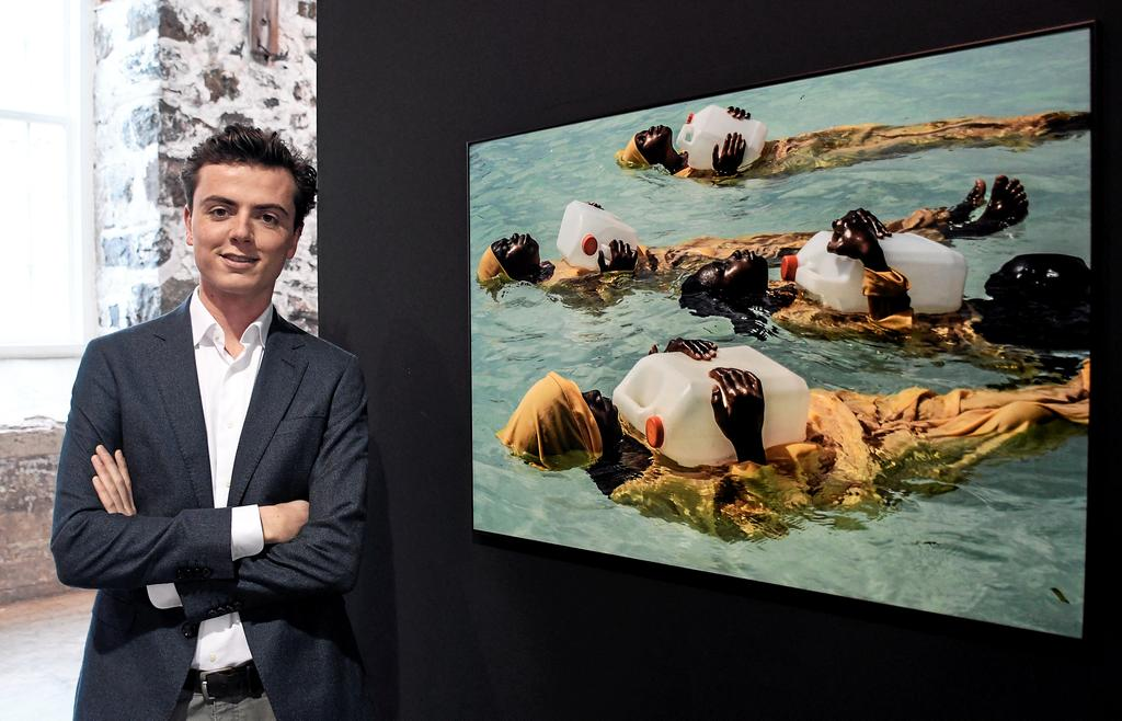 Jerzy Brinkhof, responsable et commissaire de l'exposition du World Press Photo, devant une photo de femmes qui flottent sur l'eau à l'aide de bidons. La photo d'Anna Boyiazis est des plus significatives.