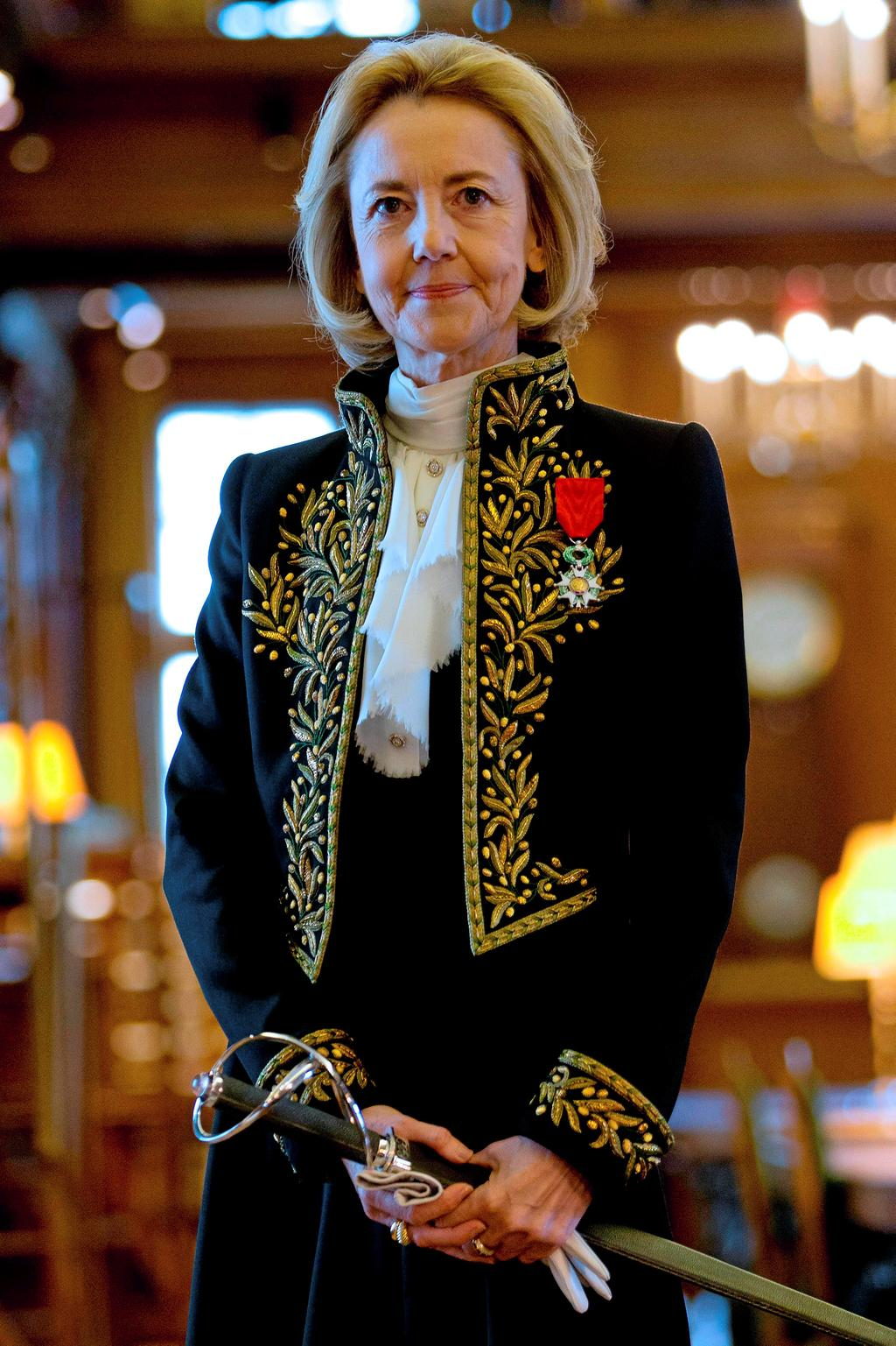 (FILES) In this file photo taken on October 23, 2014, new member of the Academie Francaise (French Academy), author Dominique Bona, wearing her Academician suit and holding her sword, poses in the institution's library following her reception ceremony in Paris. - The official guardians of the French language may be about to end centuries of male linguistic dominance by allowing more feminine words for professions. (Photo by KENZO TRIBOUILLARD / AFP)